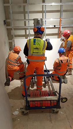 Construction team fitting GRC panels with a hoist onto aluminium cladding frame